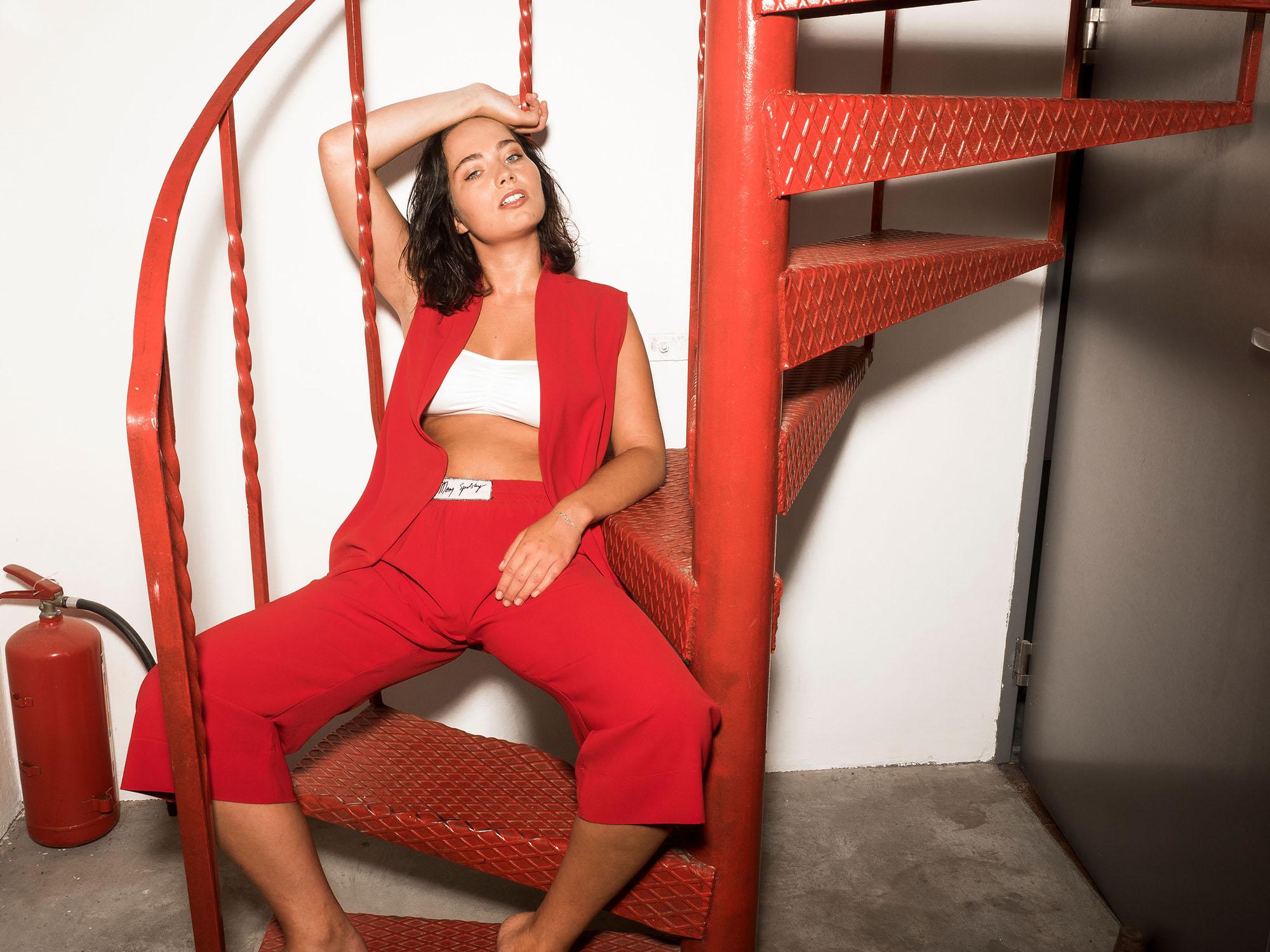 Na bialej scianie stoja czerwone schody a obok nich po lewej stronie stoi czerwona gasnica na schodach ciedzi mloda kobieta brunetka ubrana w bialy top czerwona kamizelke i czerwone spodnie